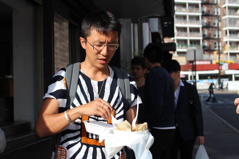 Lei eating steamed dumplings on the corner of Kissena Blvd and Main Street